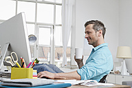 Man at home sitting at desk with computer - RBYF000356