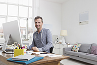 Man at home sitting at desk with computer - RBYF000365