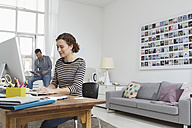 Man and woman at home sitting at desk with computer - RBYF000475