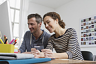 Couple at home sitting at desk shopping online - RBYF000371