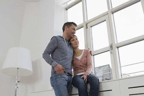 Smiling couple embracing at the window - RBYF000377