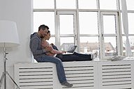 Couple sitting on windowsill using laptop - RBYF000478