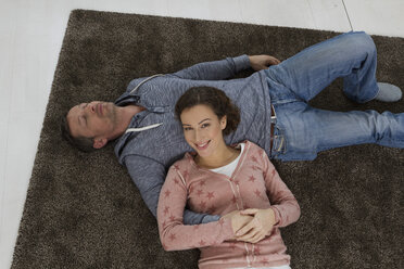 Happy couple lying on the floor - RBYF000388