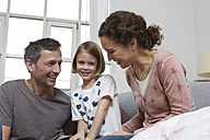 Mother, father and daughter at home on couch - RBYF000411