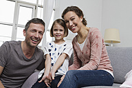 Mother, father and daughter at home on couch - RBYF000414