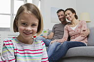 Blond girl in living room with parents in background - RBYF000423