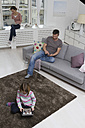 Mother, father and daughter using portable devices in living room - RBYF000481