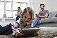 Mother, father and daughter using portable devices in living room - RBYF000484