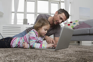 Father and daughter using laptop on carpet in living room - RBYF000485