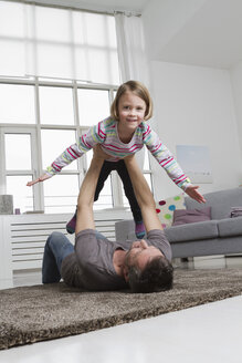 Playful father and daughter in living room - RBYF000488