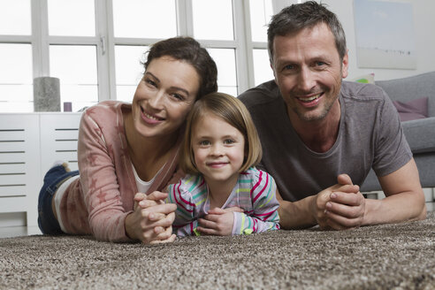 Happy mother, father and daughter lying on carpet in living room - RBYF000491
