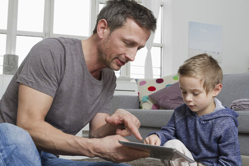 Father and son using tablet computer in living room - RBYF000494