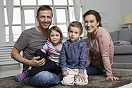 Happy family of four in living room - RBYF000497