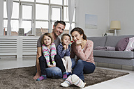 Happy family of four in living room - RBYF000499