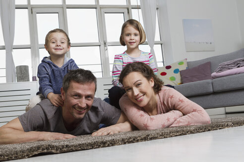 Happy family of four in living room - RBYF000502