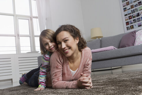 Happy mother and daughter lying on carpet in living room - RBYF000428