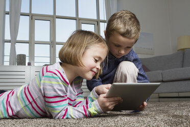 Brother and sister using tablet computer on carpet in living room - RBYF000434