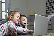 Brother and sister using laptop on carpet in living room - RBYF000437