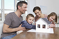 Family of four looking at house model - RBYF000451
