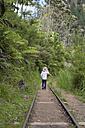 New Zealand, North Island, Waikato, Karangahake Gorge, girl walking on rail track in the rainforest - JB000029