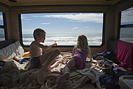 New Zealand, North Island, Bay of Plenty, Tauranga, Papamoa Beach, kids in motor home looking at Pacific Ocen - JB000046