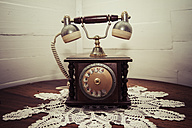 Old telephone standing on crochet tablecloth in a corner - KRP000306