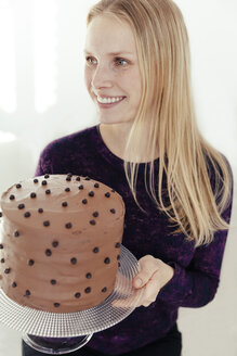 Portrait of smiling young woman holding cake stand with chocolate cake - MFF000891