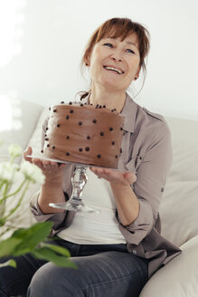 Portrait of smiling woman holding cake stand with chocolate cake - MFF000893