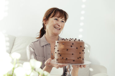 Portrait of smiling woman holding cake stand with chocolate cake - MFF000892