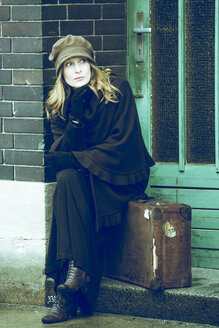 Woman sitting on her suitcase waiting - NG000077