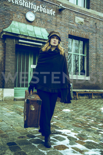 Germany, Berlin, woman carrying suitcase in front of old industrial building - NG000121 - Nadine Ginzel/Westend61