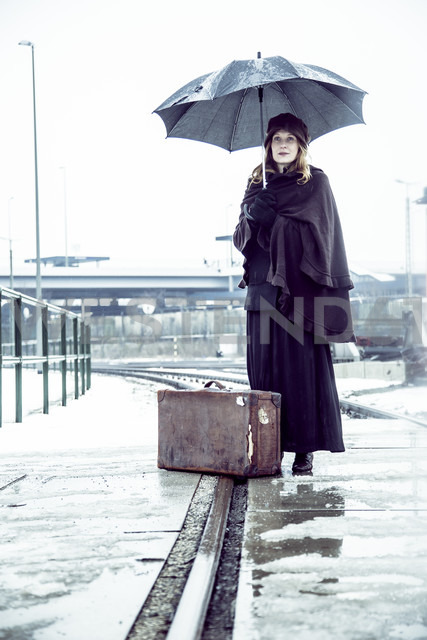 Germany, Berlin, woman with umbrella and old suitcase waiting at platform in winter - NG000083 - Nadine Ginzel/Westend61