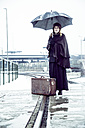 Germany, Berlin, woman with umbrella and old suitcase waiting at platform in winter - NG000083