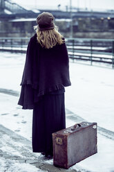 Germany, Berlin, woman with umbrella and old suitcase waiting at platform in winter - NG000085