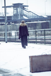 Germany, Berlin, woman with old suitcase waiting at platform in winter - NG000089