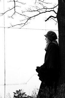 Woman leaning against tree trunk - NG000092