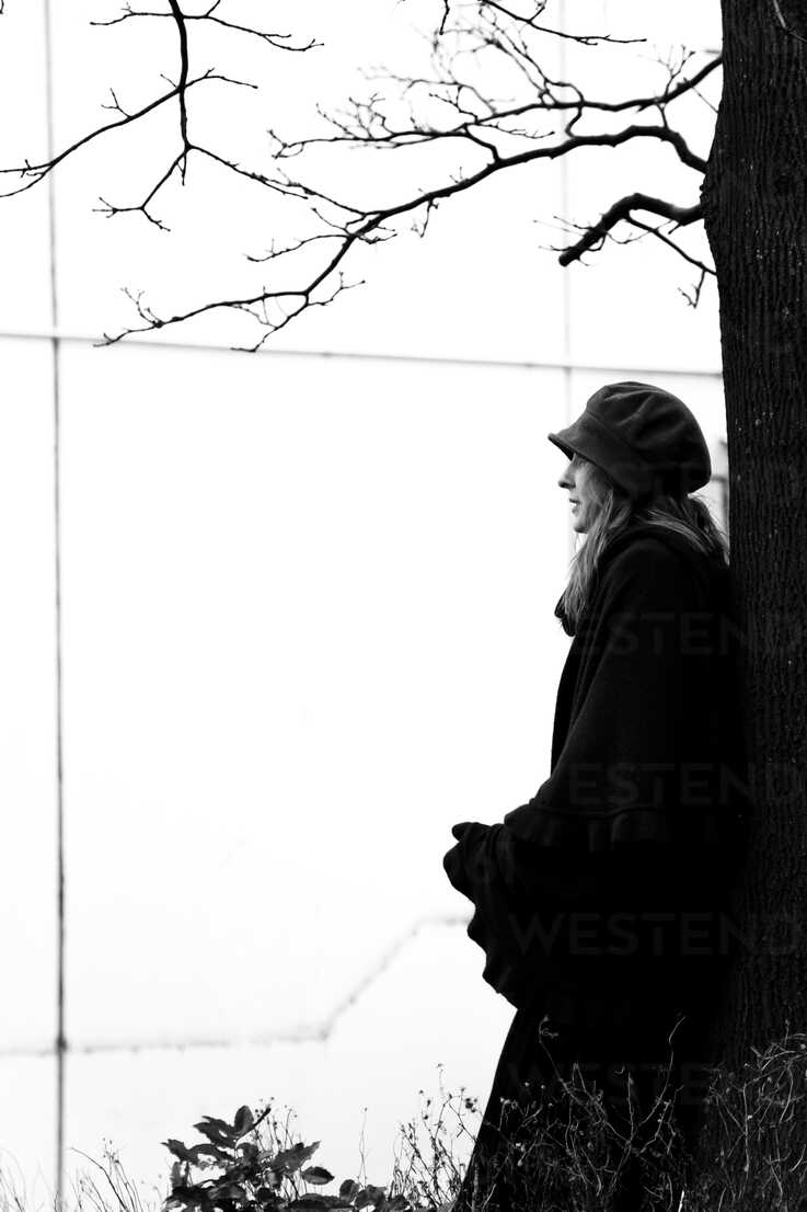 Woman leaning against tree trunk - NG000092 - Nadine Ginzel/Westend61