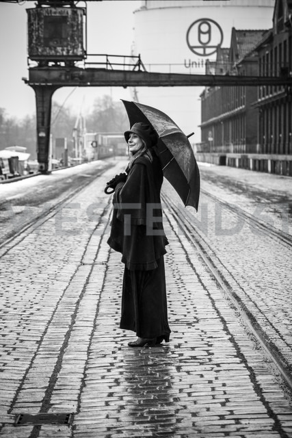 Germany, Berlin, woman with umbrella watching buildings at industrial harbour - NG000096 - Nadine Ginzel/Westend61