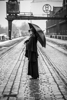 Germany, Berlin, woman with umbrella watching buildings at industrial harbour - NG000096