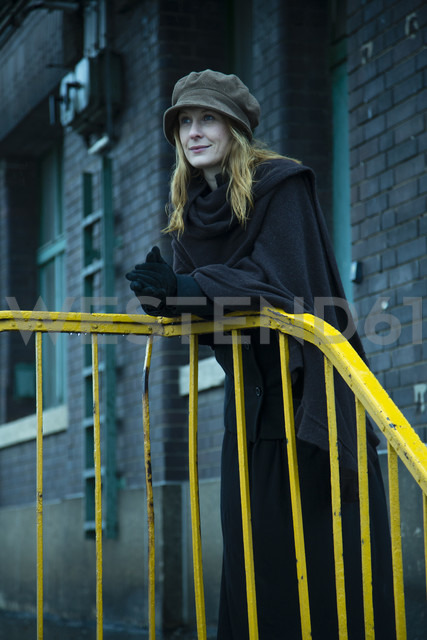 Germany, Berlin, woman leaning on yellow railing - NG000100 - Nadine Ginzel/Westend61