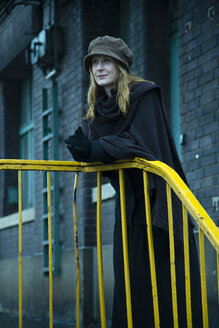 Germany, Berlin, woman leaning on yellow railing - NG000100