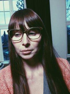 Annoyed woman with glasses looking away in room, Bonn, North Rhine-Westphalia, Germany - MEAF000217