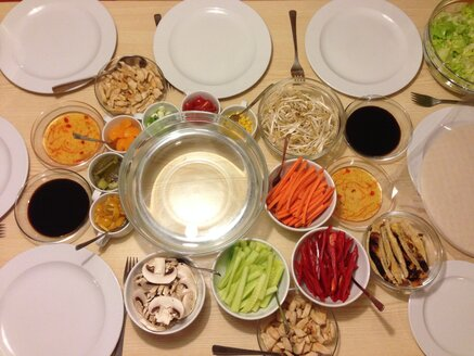 Table set with plates, various vegetables and sauces for eating Vietnamese rice rolls - MEAF000181