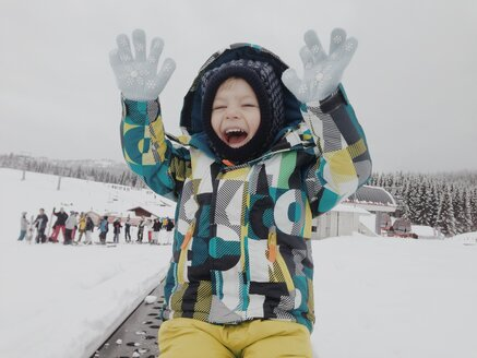 Happy boy lifting his hands in snow outfit - MEAF000184