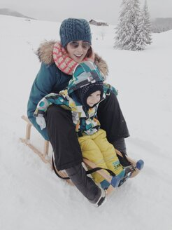 Mother and son riding down the snowy hill on a sledge in Reit im Winkl, Bavaria, Germany - MEAF000186