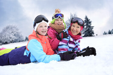 Germany, Masserberg, Mother and daughters lying in snow, smiling happily - VTF000096
