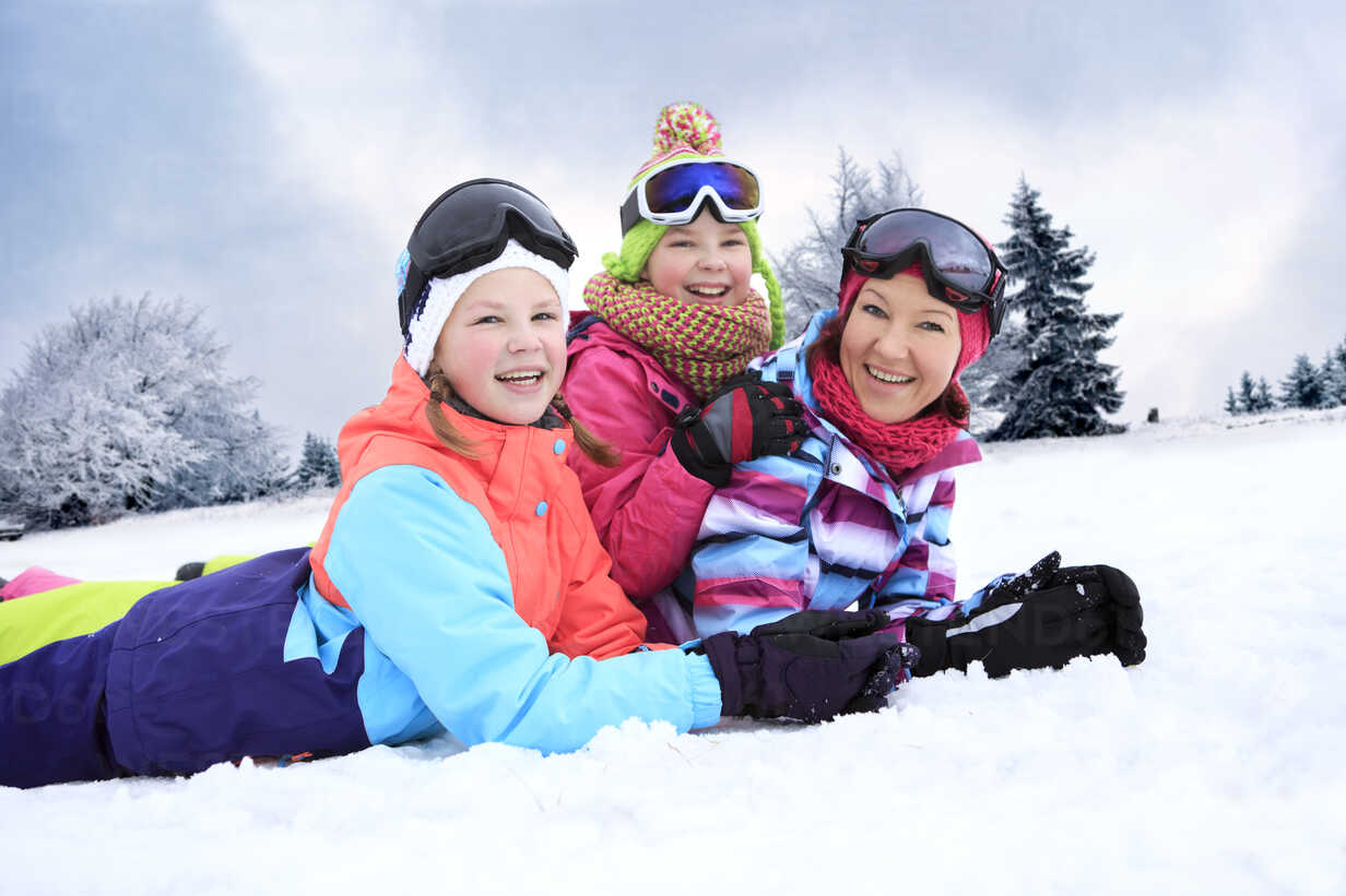 Germany, Masserberg, Mother and daughters lying in snow, smiling happily - VTF000096 - Val Thoermer/Westend61