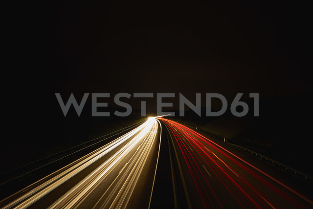 Germany, red and white lighttrails on freeway by night, long exposure - DIKF000078