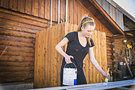 Young woman painting bars - ABAF001267