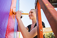 Young woman painting bars - ABAF001264